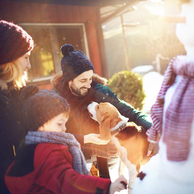 Familie baut einen Schneemann | Tiger Balm
