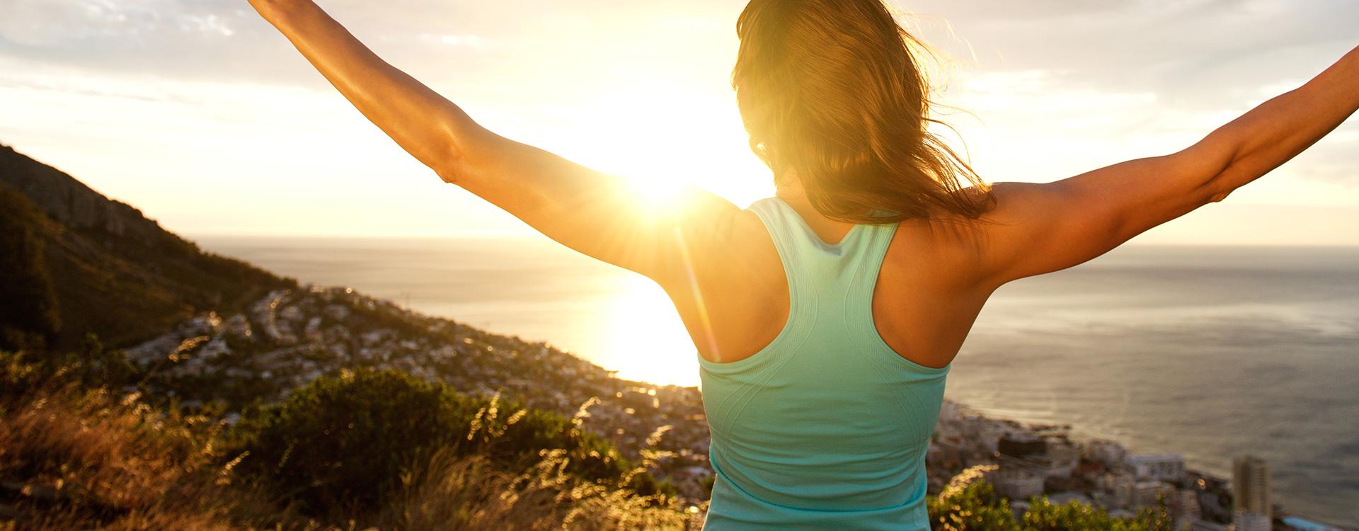 Weibliche Person steckt ihre Arme in dem Sonnenaufgang entgegen | Tiger Balm