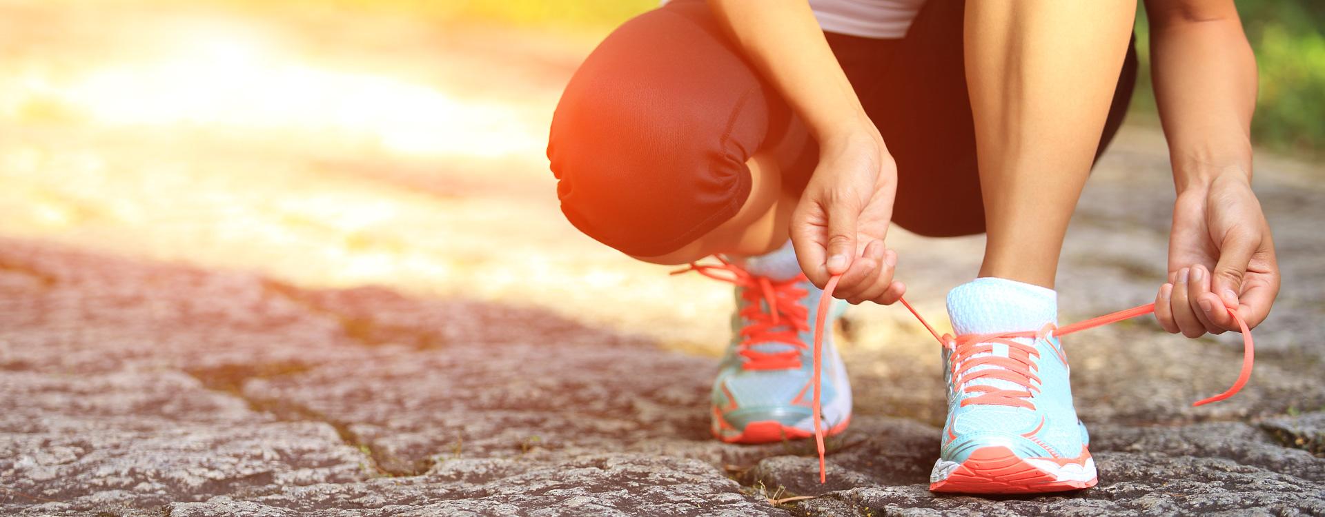 Weibliche Person schnürt Laufschuhe | Tigerbalm