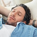 Männliche Person schläft auf dem Sofa | Tiger Balm