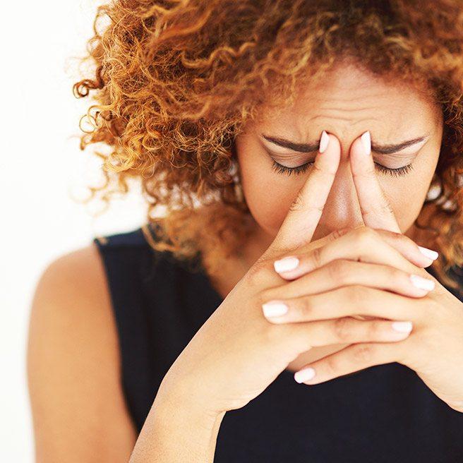 Weibliche Person hat Kopfschmerzen | Tiger Balm
