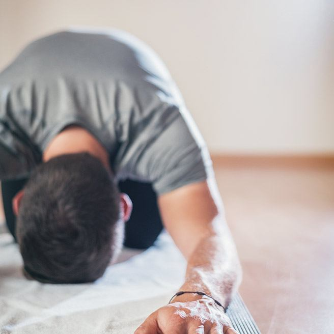 Männliche Person dehnt die Rückenmuskulatur | Tiger Balm