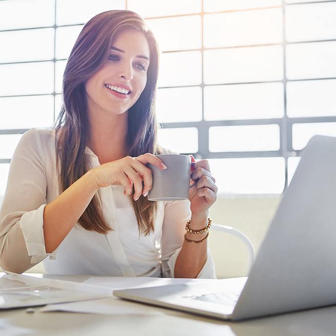 Weibliche Person sitzt am Schreibtisch und trinkt Tee | Tiger Balm