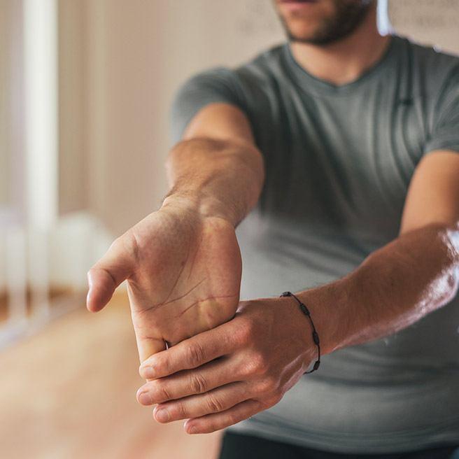 Männliche Person macht Dehnübungen | Tiger Balm